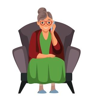 할머니가 휴대 전화를 사용하여 웃고 앉아 스마트 폰에 이야기하는 노인 여성