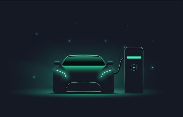 어두운 배경 ev 개념에 빛나는 녹색으로 충전 스테이션 전면보기 전기 자동차 실루엣에서 전기 자동차