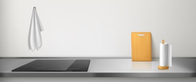 Электрическая плита на кухонной столешнице с тряпкой, бумажным полотенцем и разделочной доской