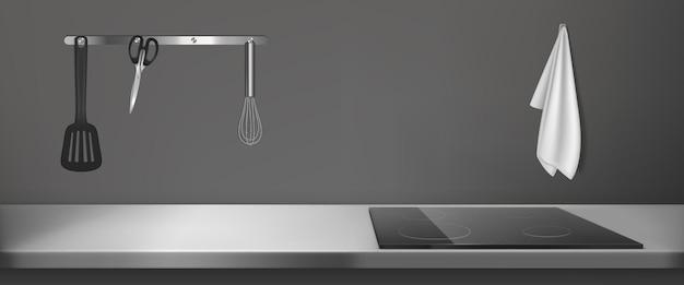 Электрическая плита на кухонной столешнице с тряпкой, венчиком, токарным станком и ножницами.