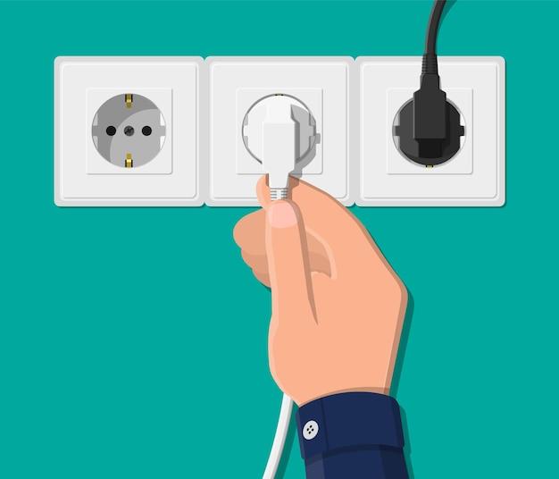 전기 콘센트와 플러그가있는 손. 전기 부품. 케이블이있는 벽면 소켓.