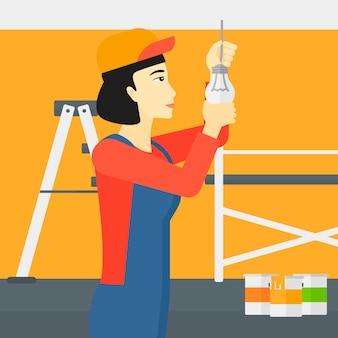 Electrician twisting light bulb.
