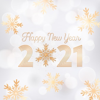 Elegant new year greeting postcard, invitation flyer or promo brochure design, happy new year card with gold snow flakes and glitter on white blurred background with golden 2021 typography poster Premium Vector