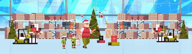 ギフトプレゼントボックスと一緒に働くサンタクロースのエルフカップルヘルパーモダンな倉庫インテリアクリスマス休暇お祝いコンセプトバナー