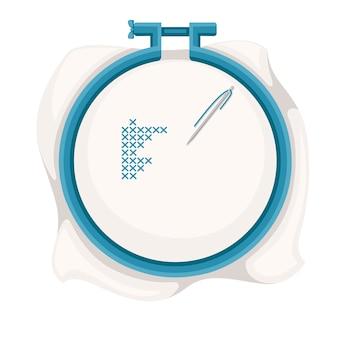 クロスステッチの刺繍フープ。青いプラスチックフープ、青い糸が付いたステンレス鋼の針。図