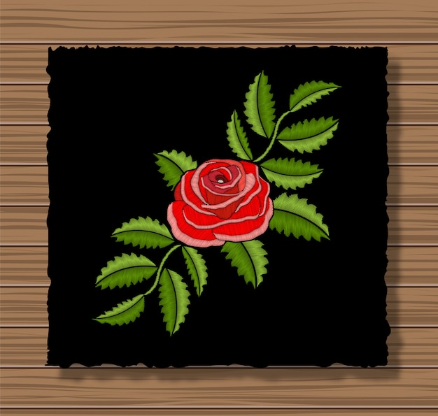 Embroidery rose on a dark flap cloth and wooden texture background. floral ornament with stitch flower and leaves