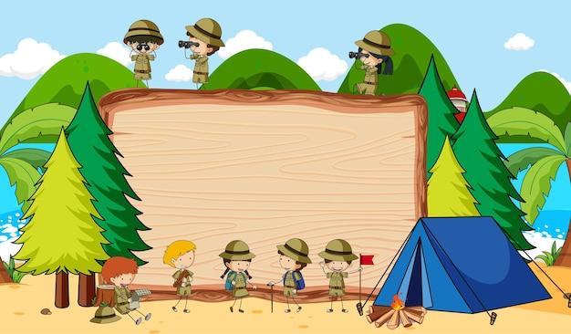 Lavagna vuota nella scena della natura con molti bambini in tema scout