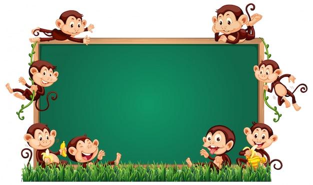 Empty blackboard template with cute monkeys on grass