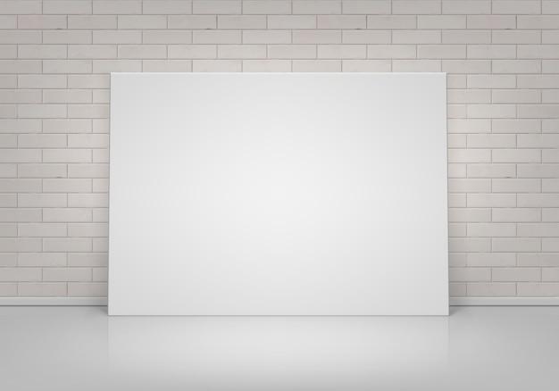 Пустой пустой белый макет плаката фоторамка, стоящая на полу с кирпичной стеной, вид спереди
