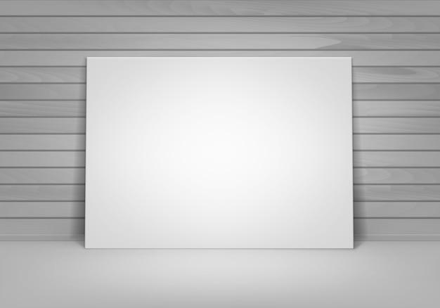 Пустой пустой белый макет фоторамки плаката, стоящего на полу с деревянной стеной, вид спереди