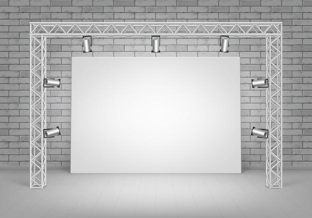 Пустой пустой белый макет плаката, стоящего на полу с серой кирпичной стеной и прожекторами, освещением, вид спереди