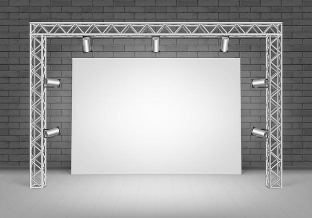 Пустой пустой белый плакат картина, стоящая на полу с черной кирпичной стеной и прожекторами, освещением, вид спереди