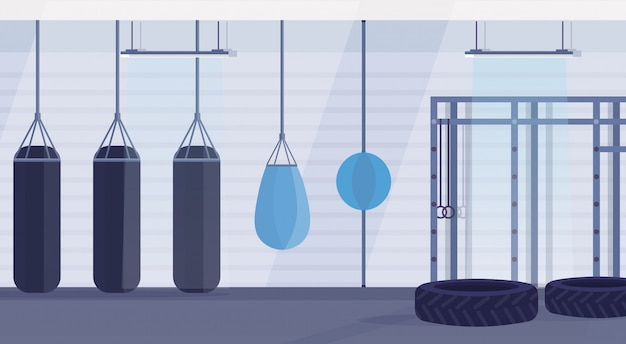 Empty boxing studio with punching bags of different shapes for practicing martial arts in gym modern fight club interior design horizontal banner flat