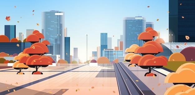 太陽の光の中で人と車の黄色の木のない空のダウンタウン秋の街