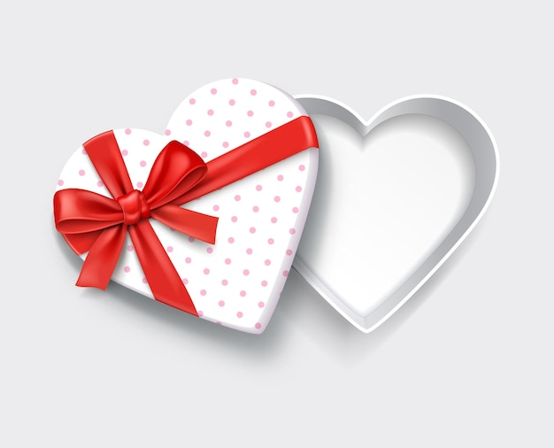 Empty open heart shaped white gift box with red ribbon.