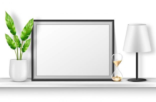 식물을 가진 백색 선반에 빈 사진 프레임 스탠드