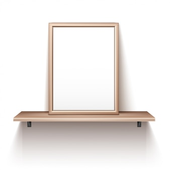 Empty photo frame standing on wooden shelf