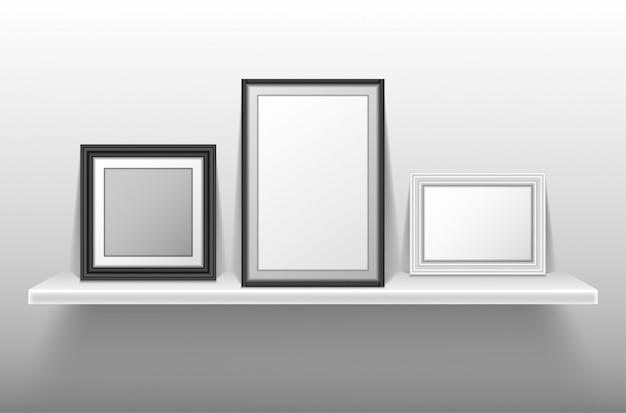 Empty photo frames standing on white shelf