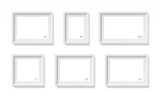 빈 그림 프레임 모형. 사진 컨테이너 템플릿. 흰 벽에 고립 된 3d 그림입니다. 종이 포스터를위한 빈 공간입니다. 객체 세트