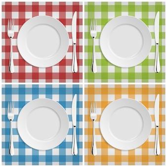 Пустая тарелка с вилкой и ножом на классической клетчатой скатерти