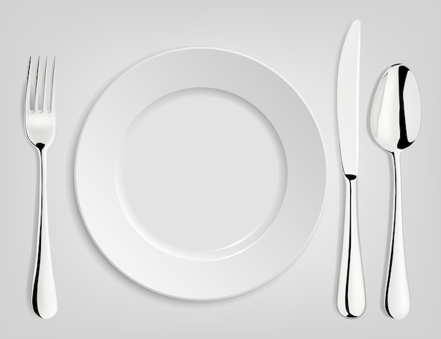 Пустая тарелка с ложкой, ножом и вилкой.