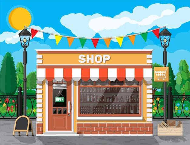 창문과 문이있는 빈 가게 앞. 유리 쇼케이스, 작은 유럽 스타일의 상점 외관. 상업, 부동산, 시장 또는 슈퍼마켓. 도시 공원, 가로등 및 나무.
