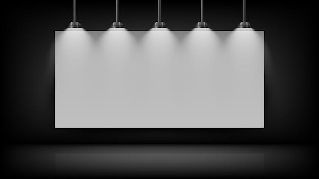 上部に電球が付いている黒い壁に空のホワイトボード