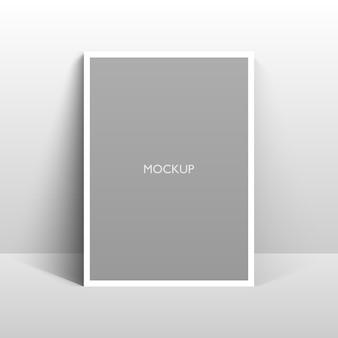 Макет пустой белой рамки на серой стене