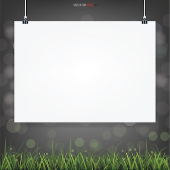 Empty white poster paper in green field area with light bluured bokeh in dark background