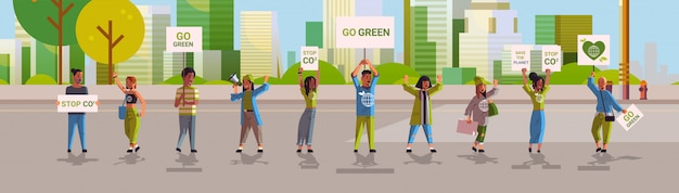 Environmental activists holding posters go green save planet strike concept protesters campaigning to protect earth demonstrating against global warming cityscape background horizontal full length