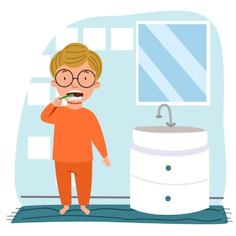 A european boy in glasses and pajamas is brushing his teeth in the bathroom.