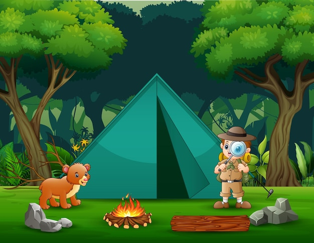 The explorer boy camping out in the forest