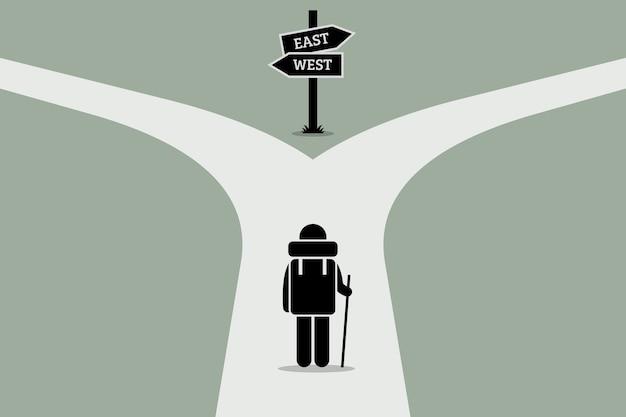 分割道路に到達するエクスプローラー。人生、意思決定、そして不確実な未来のコンセプトジャンクション。
