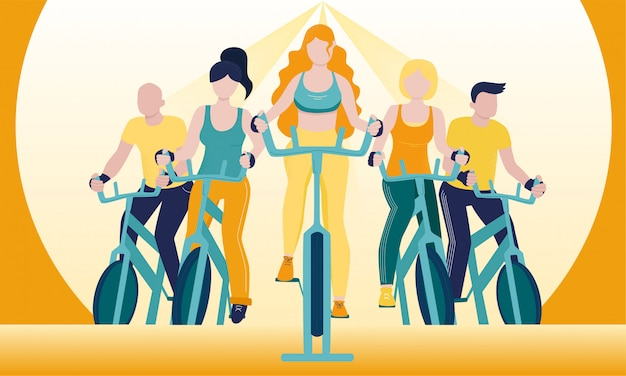 Faceless group of people on exercycles in spinning class.