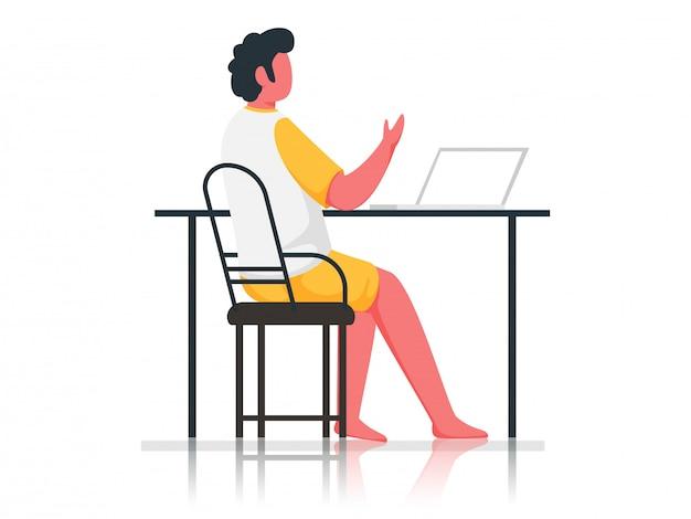 白い背景の上のテーブルでラップトップを使用して顔のない少年。