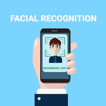 Facial recognition concept hand holding smartphone scanning of male face biometrics scan access technology concept