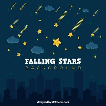 夜の都市の上に落ちる星