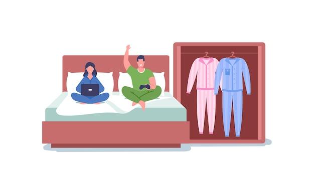 ノートパソコンとプレイステーションのジョイスティックでベッドに座っている家族のカップルは一緒に時間を過ごします。家庭服、快適なパジャマ、ナイトウェアを着た男性と女性のキャラクター。漫画の人々のベクトル図