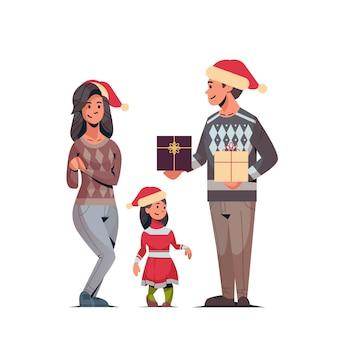 サンタの帽子をかぶった家族のギフトプレゼントボックス両親とメリークリスマスを祝う娘幸せな新年冬の休日のコンセプトイラスト
