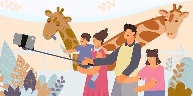 動物園でキリンと一緒に自撮り棒で家族を撮影