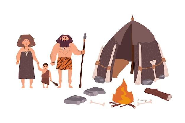고대인, 원시인, 원시인 또는 고대 인간의 가족. 어머니, 아버지, 아들이 거주지와 모닥불 옆에 서 있습니다. 석기 시대 만화 캐릭터. 플랫 다채로운 벡터 일러스트 레이 션