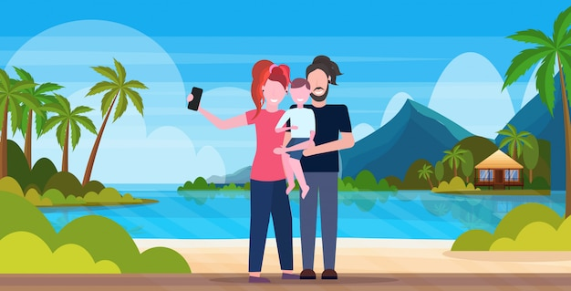 Семья на пляже, принимая селфи фото на смартфон камеры летние каникулы концепция мать отец и сын вместе тропический остров приморский фон полная длина горизонтальный