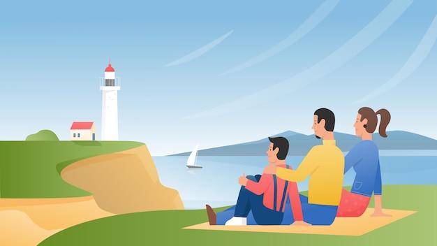 家族は海岸の緑の芝生に座って、自然の風景と灯台の景色を楽しみます