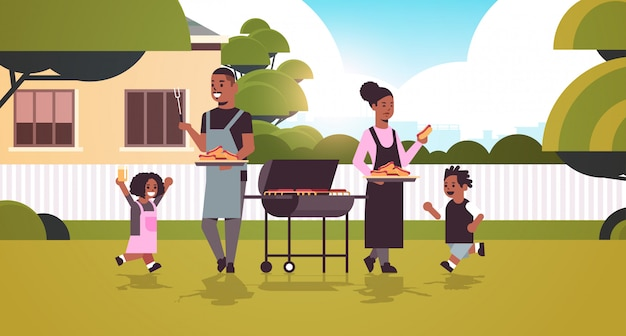 Family preparing hot dogs on grill