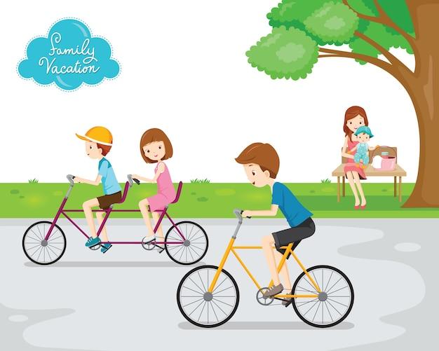 Семья отдыхает в общественном парке, дети катаются на велосипеде, мама и ребенок сидят на скамейке под деревом