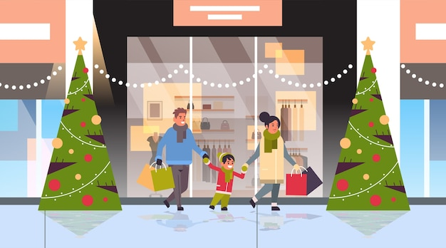 Family walking with colorful paper bags merry christmas happy new year shopping concept parents with child holding purchases modern mall exterior