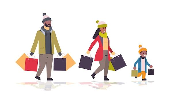 カラフルな紙袋を持って歩く家族メリークリスマス新年あけましておめでとうございます冬のショッピングコンセプト子供を持つ親の購入