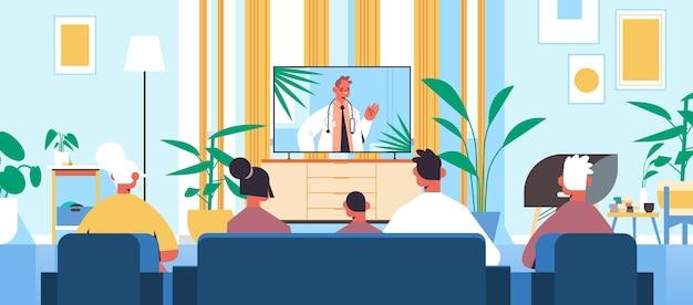 家族のテレビ画面で男性医師とのオンラインビデオ相談を見てヘルスケアの遠隔医療医療のアドバイスのコンセプト