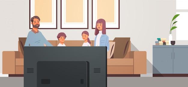 家族が一緒にリビングルームのインテリアで時間を過ごす子供たちとテレビの毎日のニュース番組の親を見て