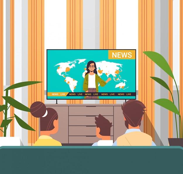 家族一緒にリビングルームのインテリアを一緒に過ごす息子とテレビの毎日のニュース番組の両親